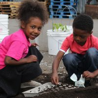 Nylinn and Raili plant seeds at Marion Polk Food Share